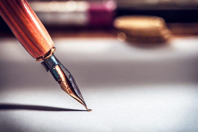 image of putting a pen to paper