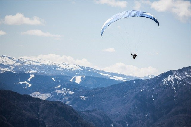 image of person parasailing over mountains